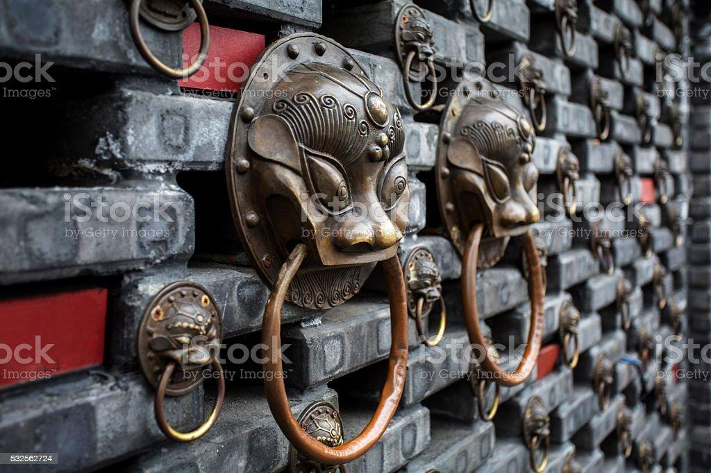 iron dragon knocker decorated on brick wall stock photo