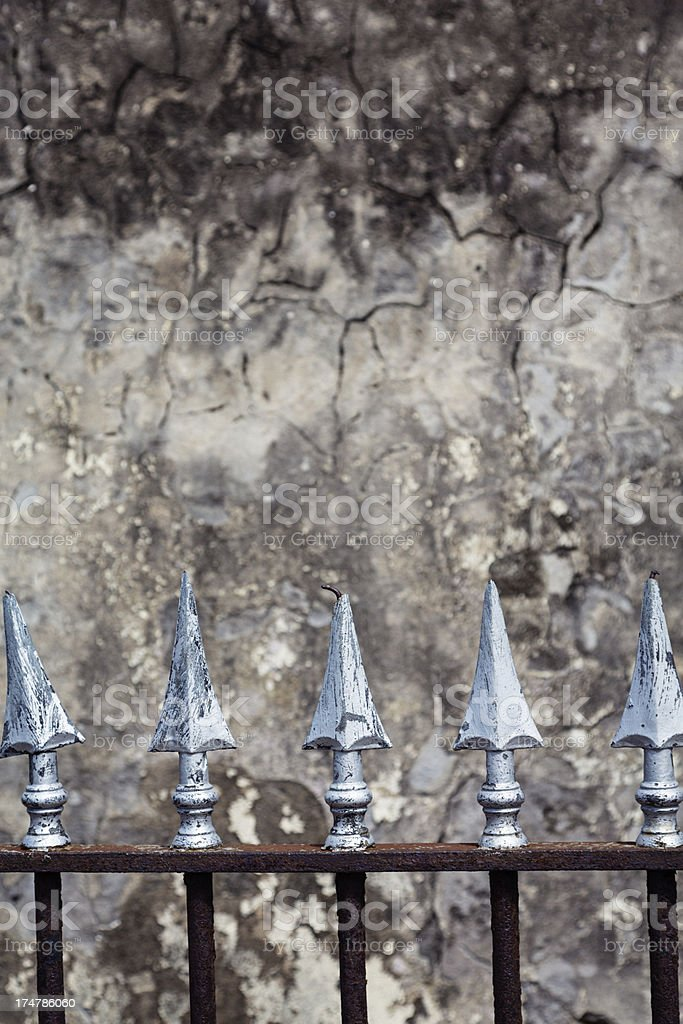Iron Fence in Front of Textured Marble Wall royalty-free stock photo