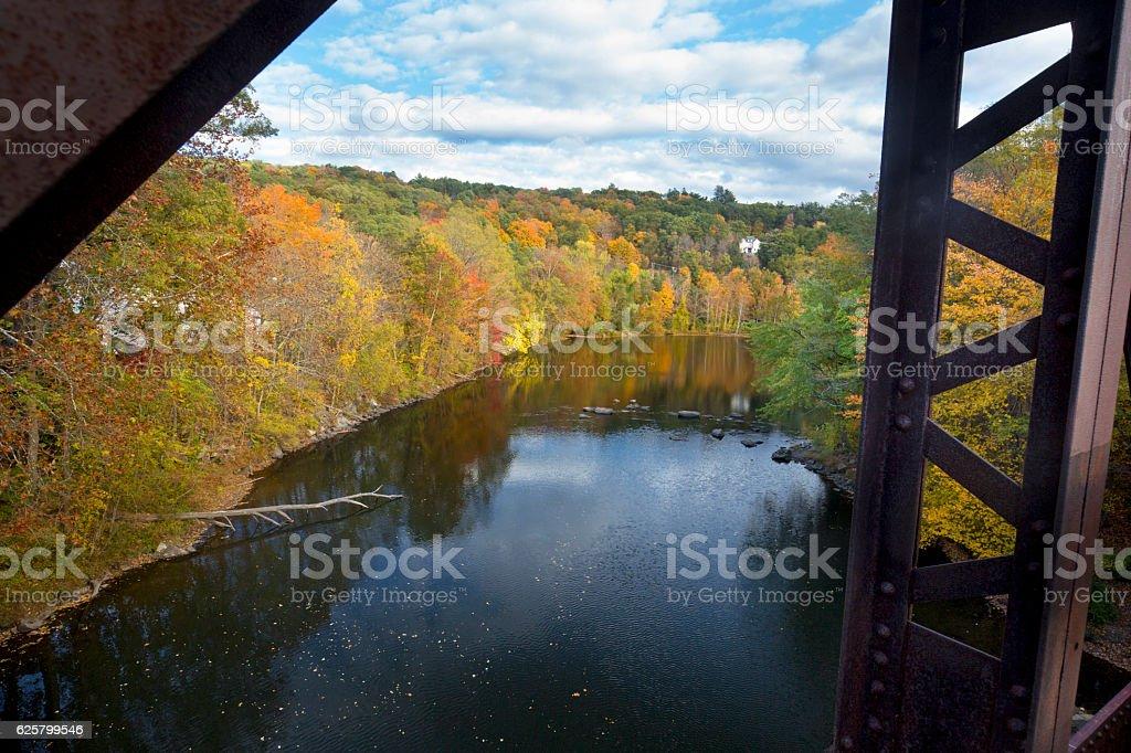 Iron girders frame a colorful Farmington River in Canton, Connec stock photo