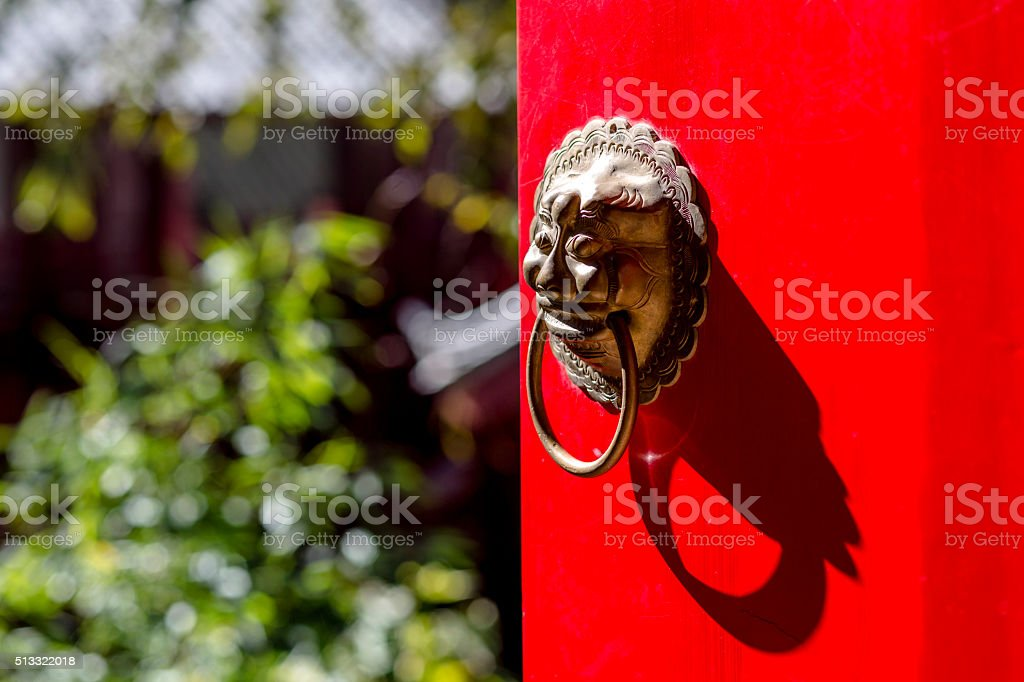 iron lion knocker on red door stock photo