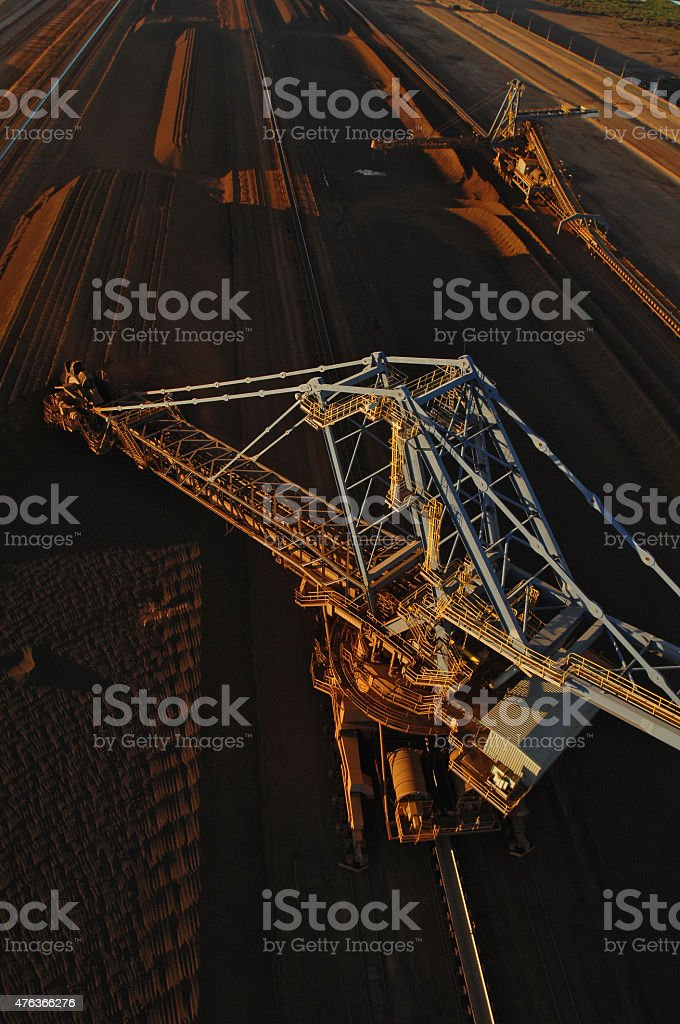 Iron ore reclaimer and iron ore stockpile stock photo