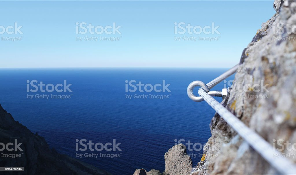 Iron piton in a granite rock with rope royalty-free stock photo