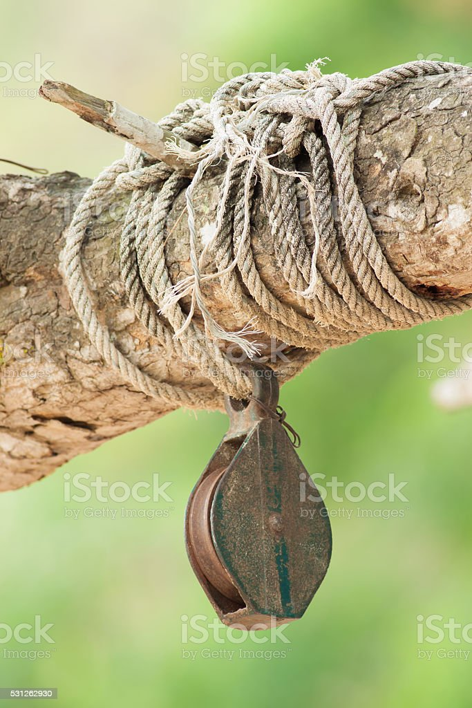 Iron reel with the rope tied on tree stick royalty-free stock photo