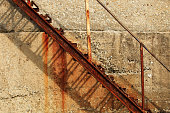 Iron rusty abandoned staircase on the background of a concrete