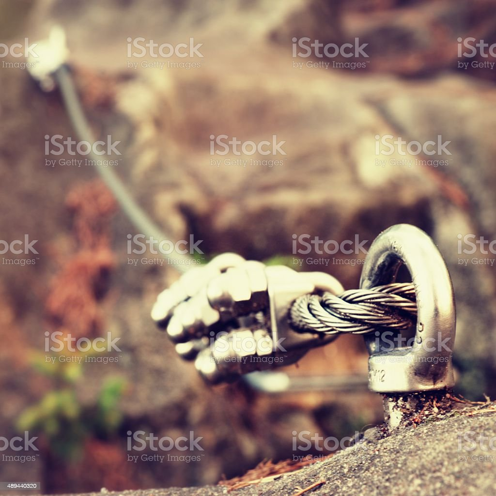 Iron twisted rope streched between rocks in climbers patch. stock photo
