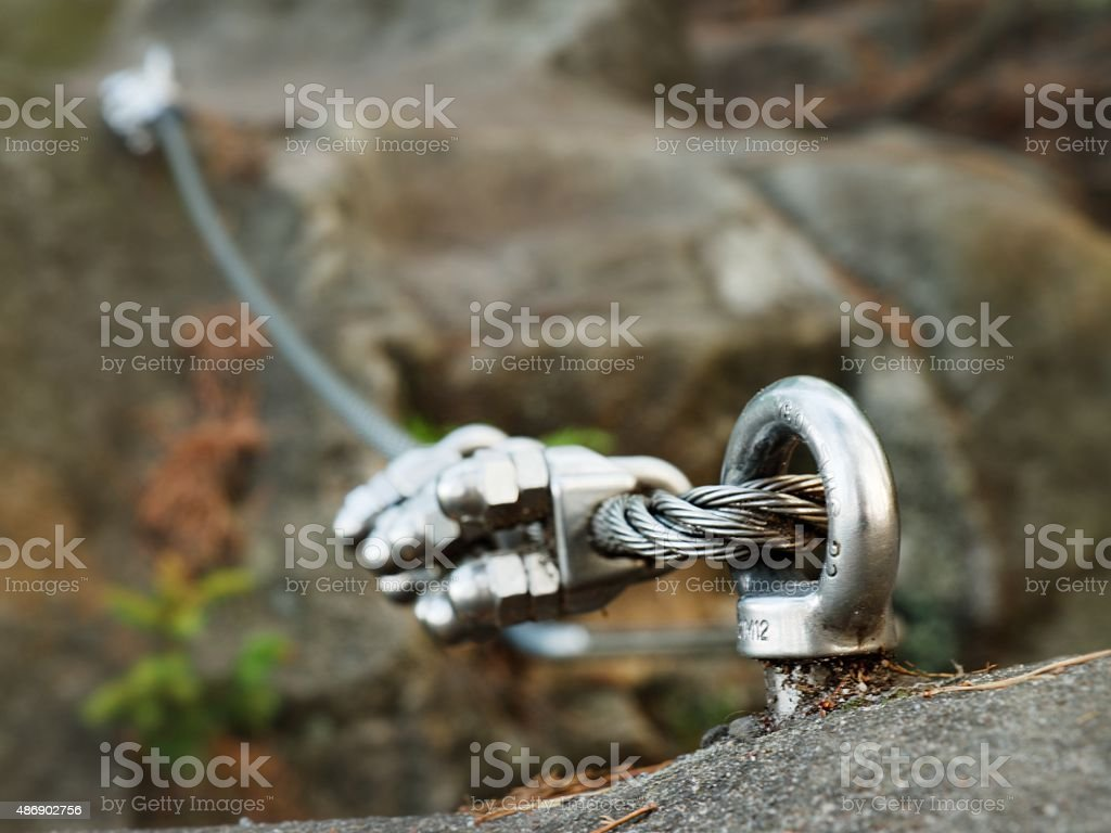 Iron twisted rope streched between rocks in climbers path stock photo