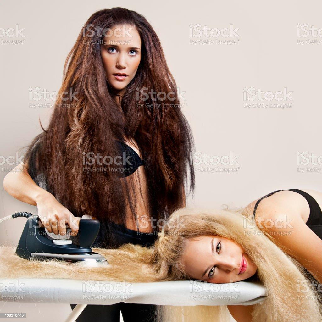 Ironing frizzy hair stock photo
