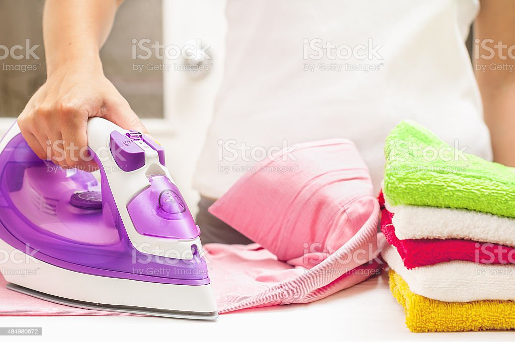 Ironing on the table at home stock photo