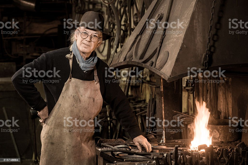 Ironworker forging hot iron in workshop stock photo