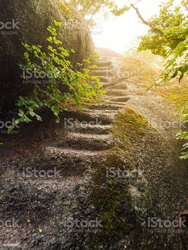 Irregular natural steps carved in the granite rock stock photo