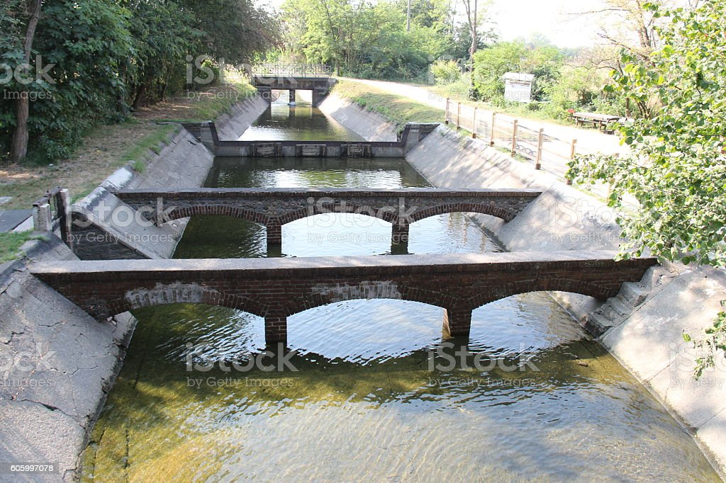 Irrigation duct with flowing water in northern Italy stock photo