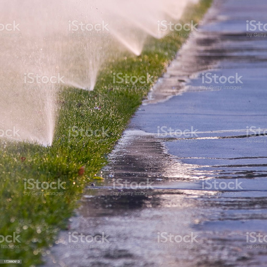 Irrigator wasting water while watering the grass stock photo