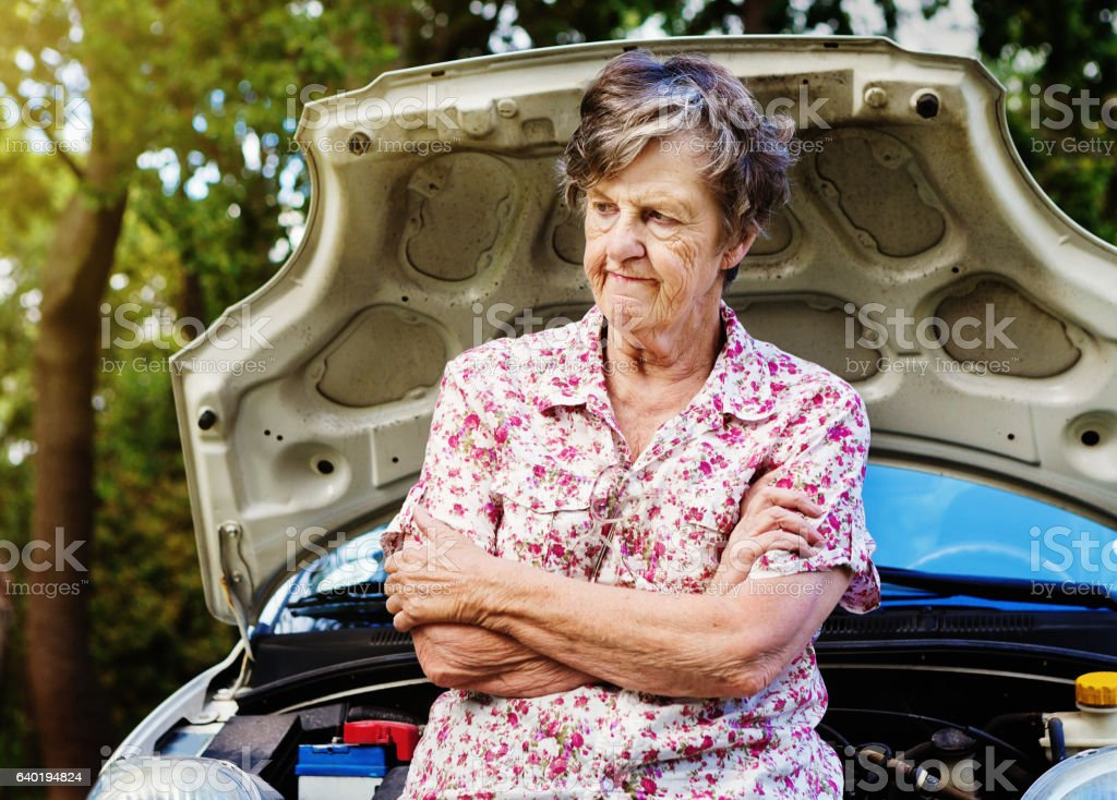 Irritated and frustrated old woman with broken-down car waits impatiently stock photo