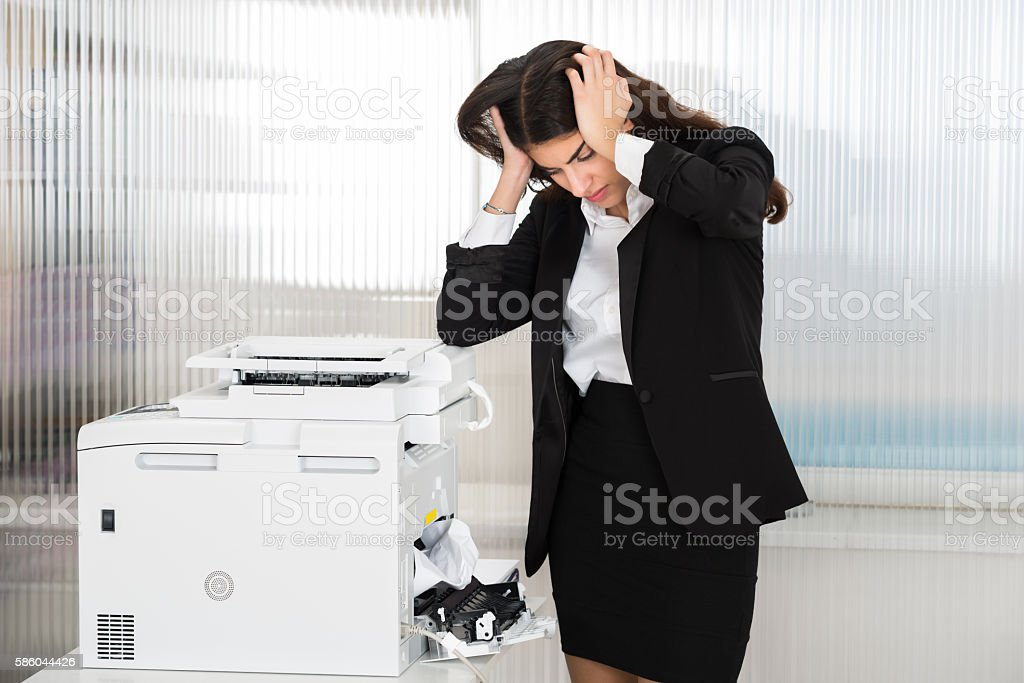 Irritated Businesswoman Looking At Paper Stuck In Printer stock photo