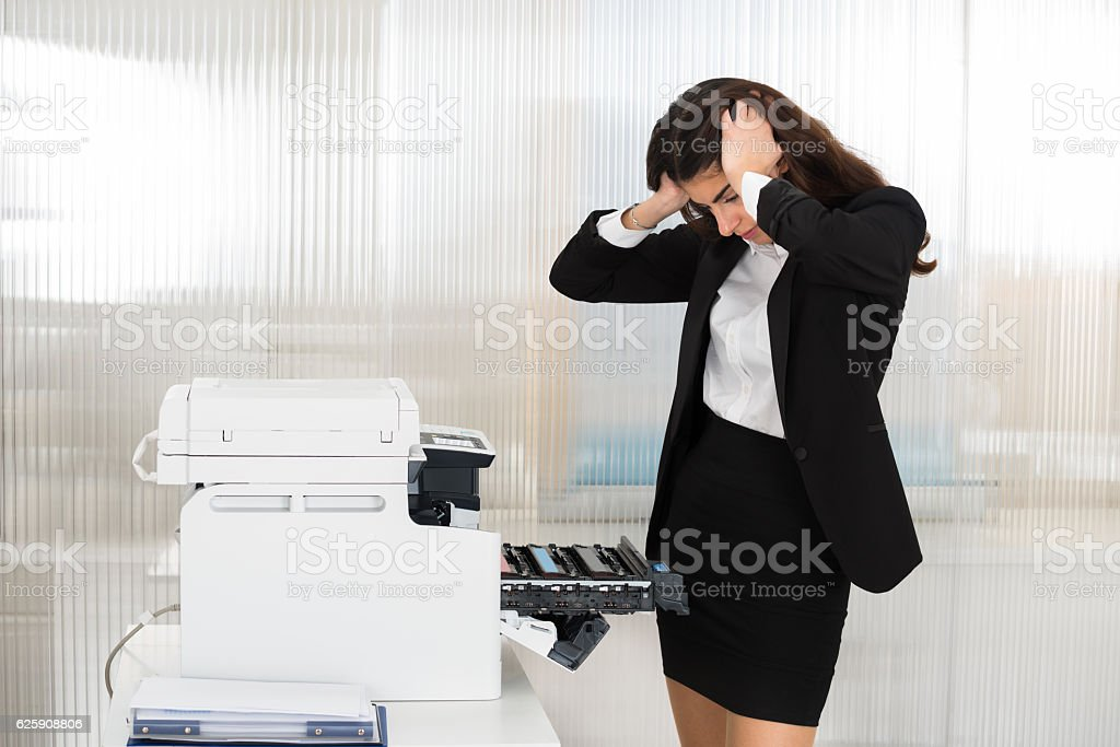 Irritated Businesswoman Looking At Printer Machine At Office stock photo