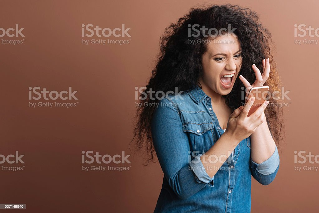 Irritated girl crying at phone stock photo