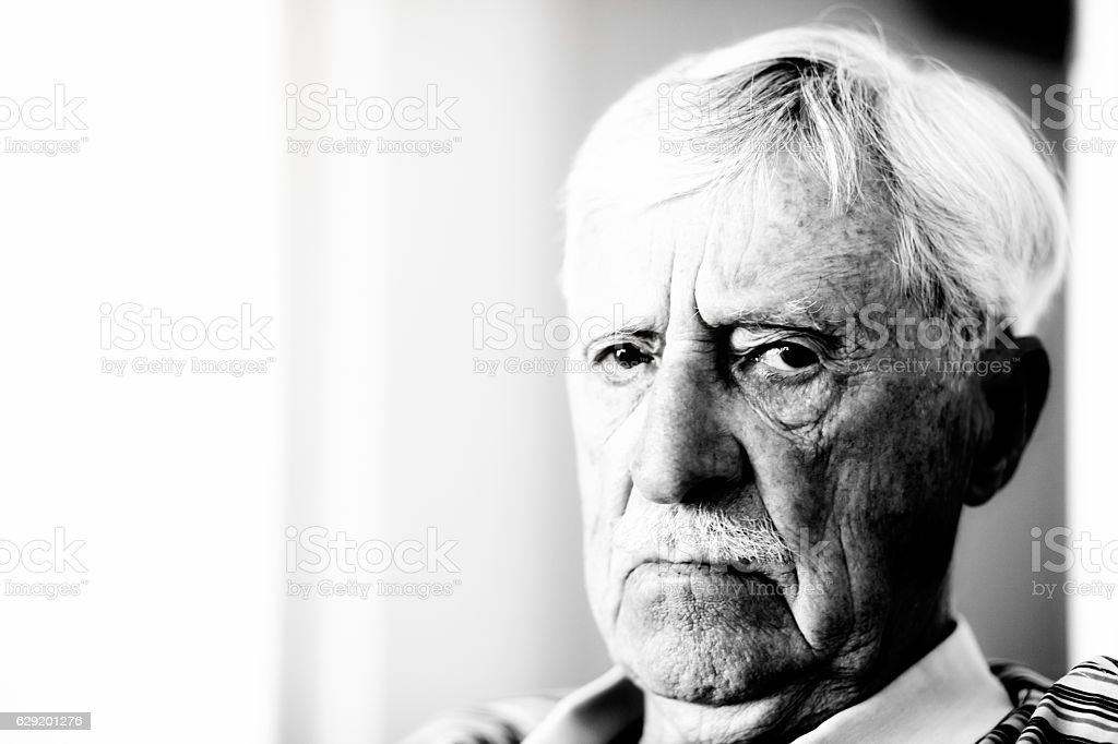 Irritated or senile old man stares at camera, frowning stock photo