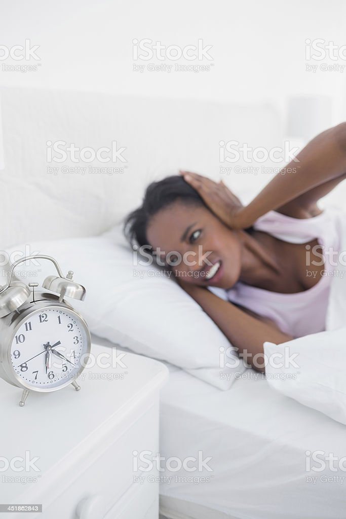 Irritated woman blocking her ears from alarm clock noise stock photo