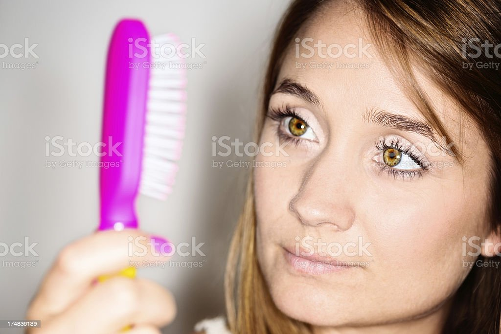 Is that dandruff? Beautiful but worried blonde looks at hairbrush royalty-free stock photo
