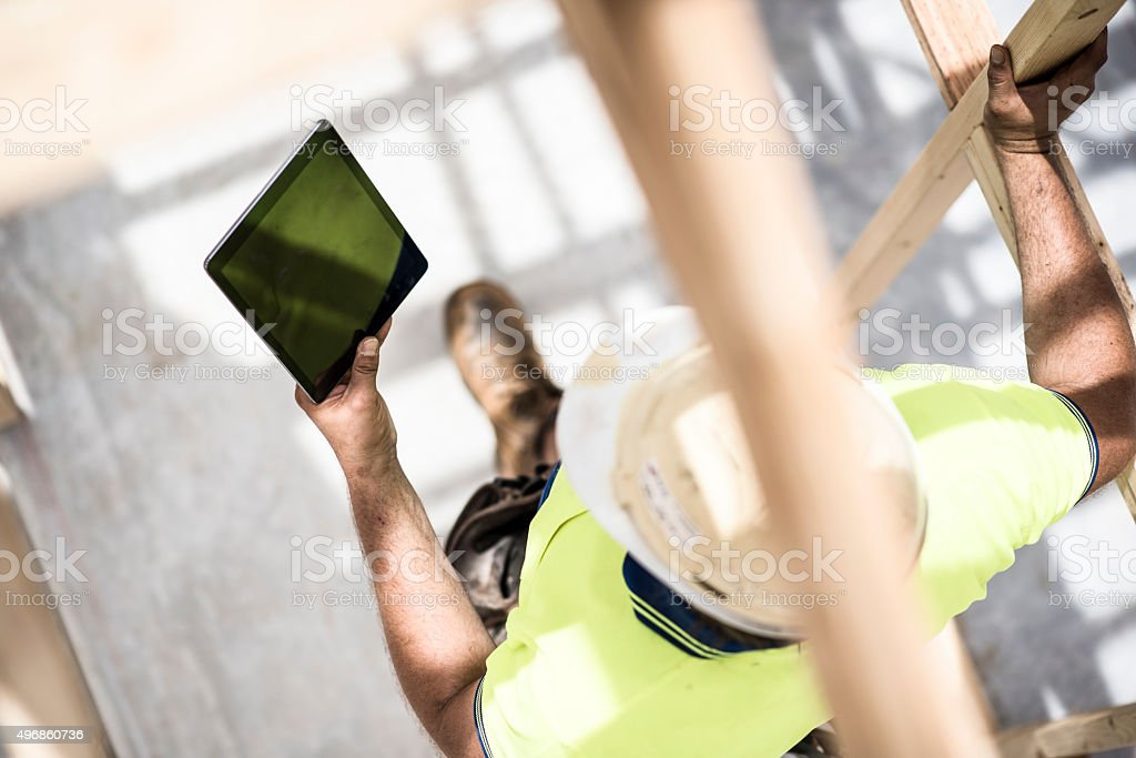 Construction worker checking house plans on digital tablet