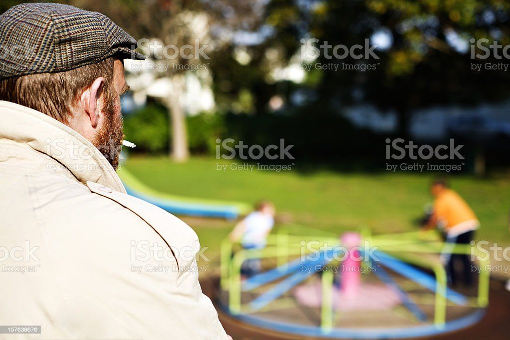 Is this a pedophile? Man watching children in park playground stock photo