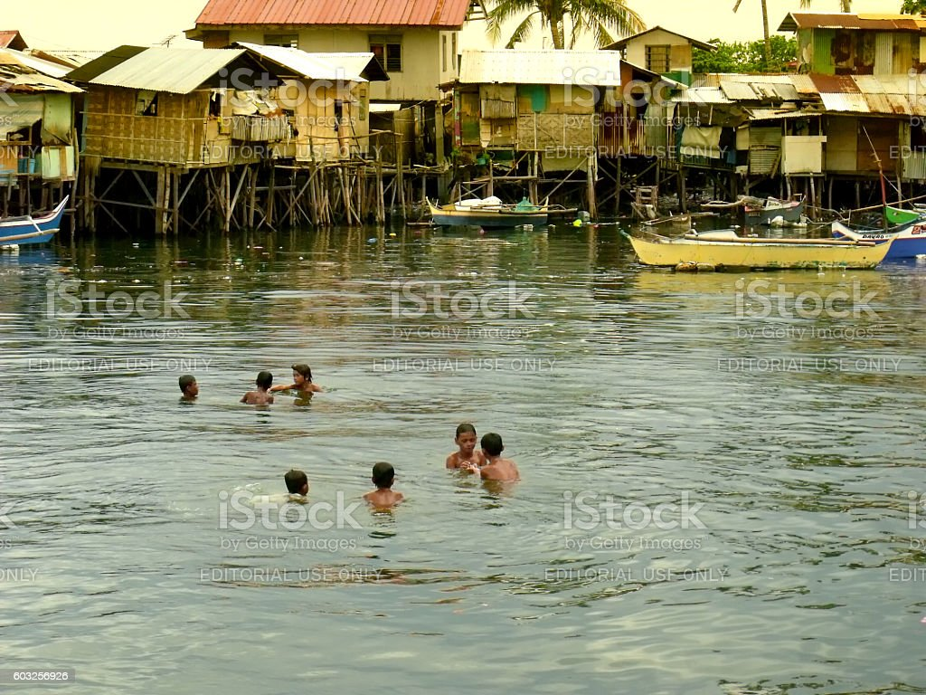 Isla Verde shantytown with children swimming stock photo