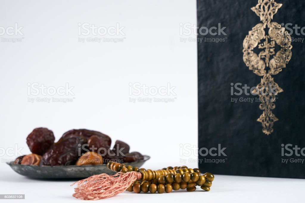 Islamic Holy Book Quran/ Kuran With wooden prayer beads Rosary and dry Dates Over white Background with copy space stock photo