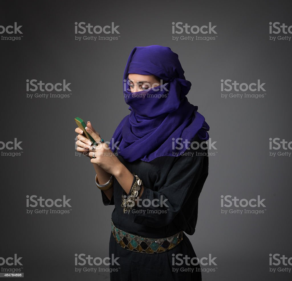 Islamic woman using phone stock photo