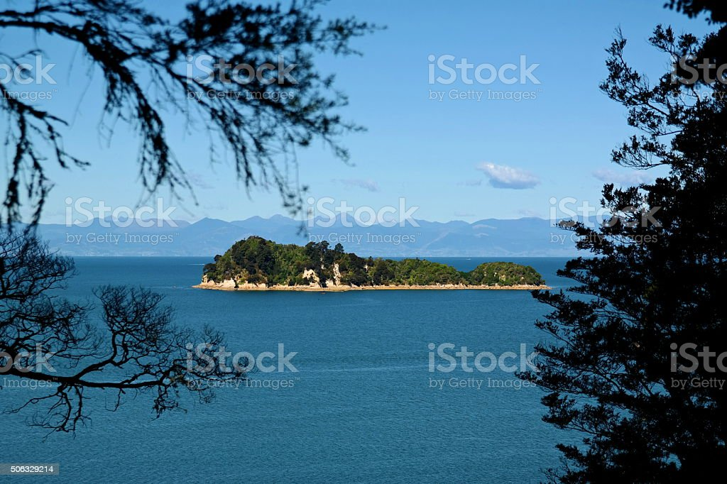 Island framed by silhouetted trees stock photo
