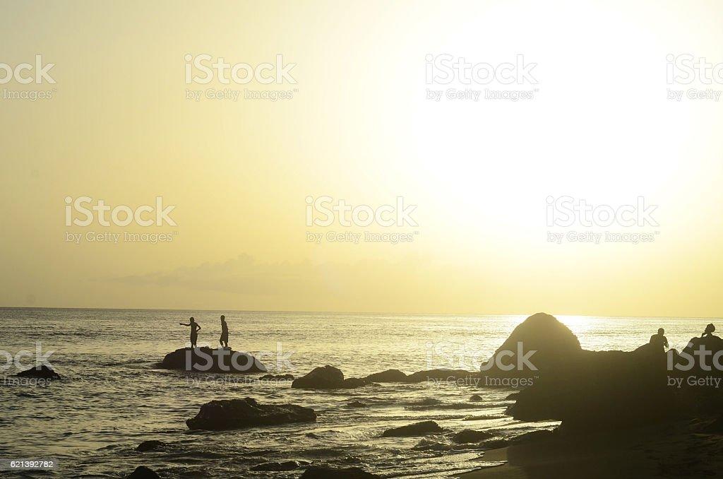 island life, fun fishing and golden sunset boys silhouette stock photo