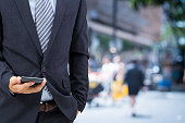 isolated business man hold the smartphone on the street