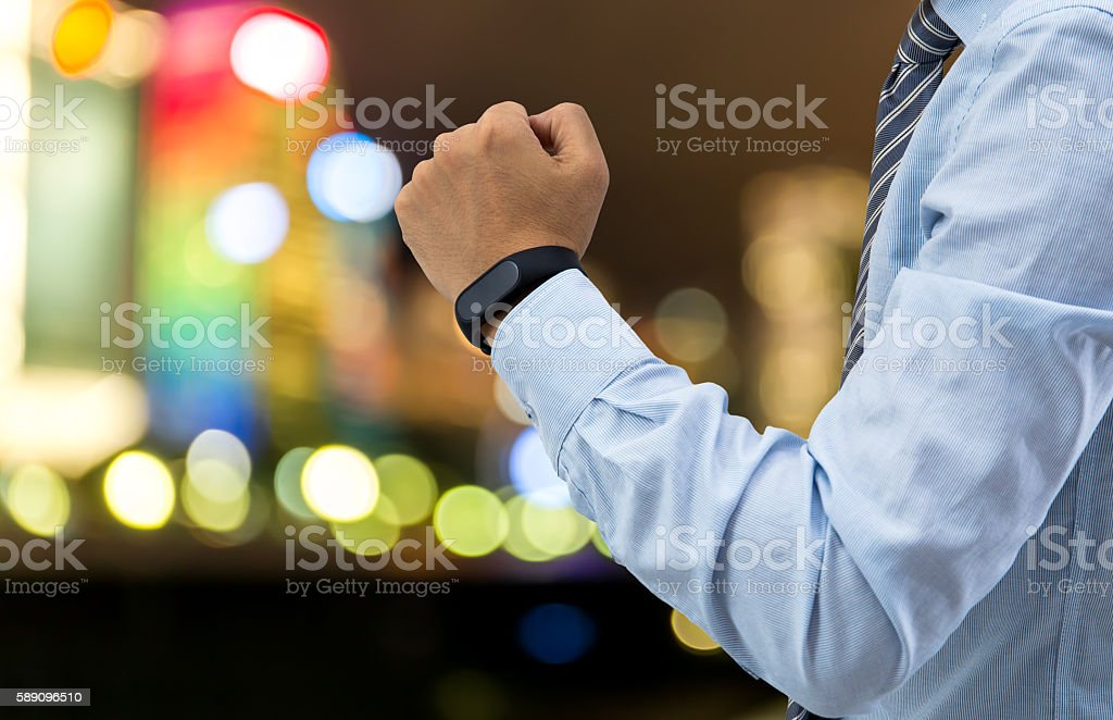 isolated business man with smart wristband and smartphone stock photo