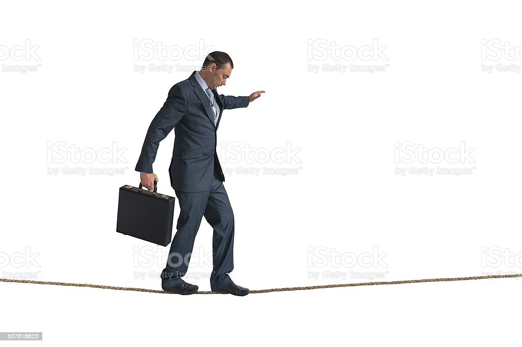 isolated businessman balancing tightrope stock photo