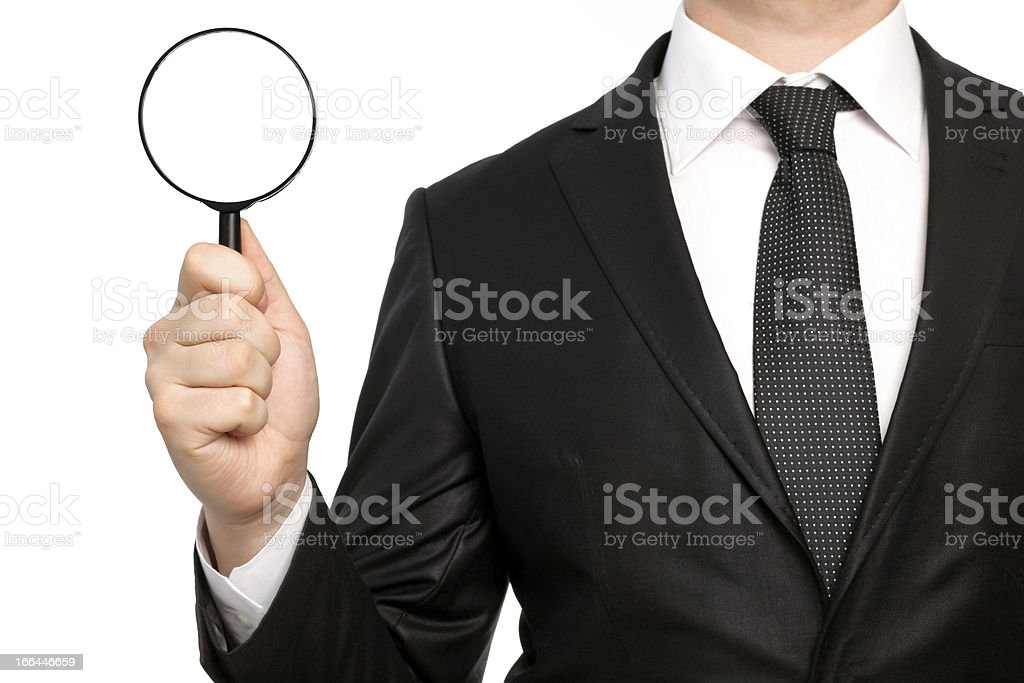 isolated businessman in suit holding a magnifying glass royalty-free stock photo