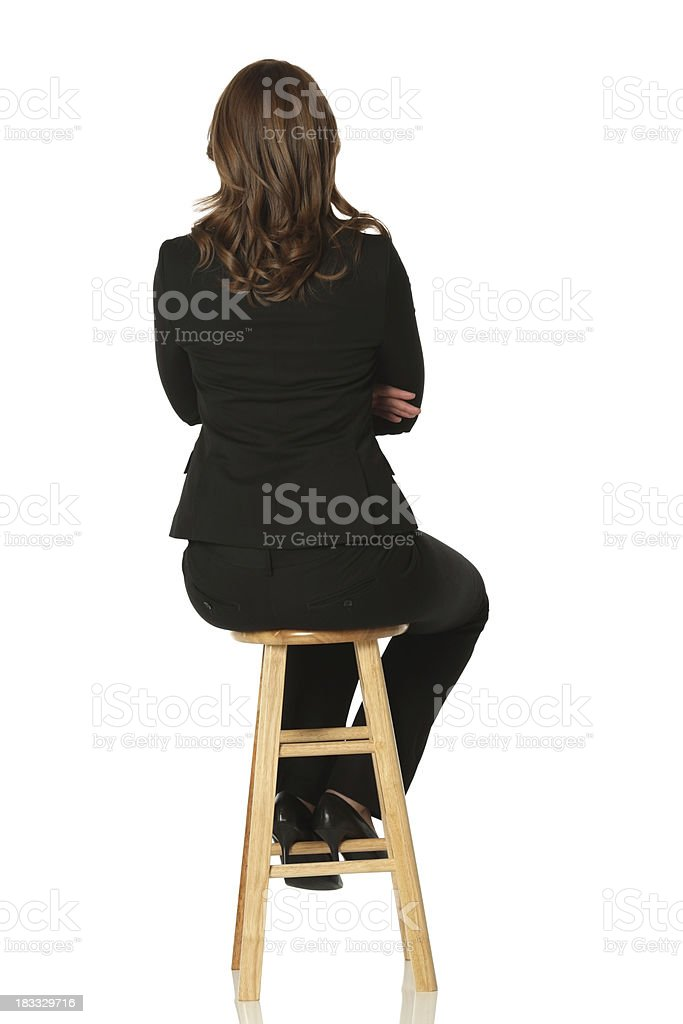 Isolated businesswoman sitting on a stool facing away royalty-free stock photo