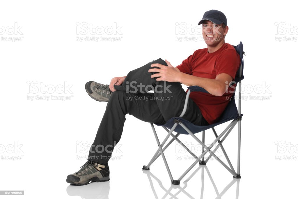 Isolated casual man sitting in camping chair stock photo