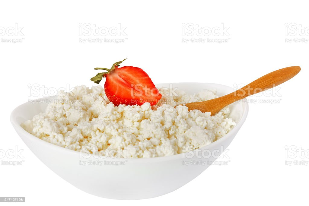 isolated cottage cheese with a strawberry and the wooden spoon stock photo