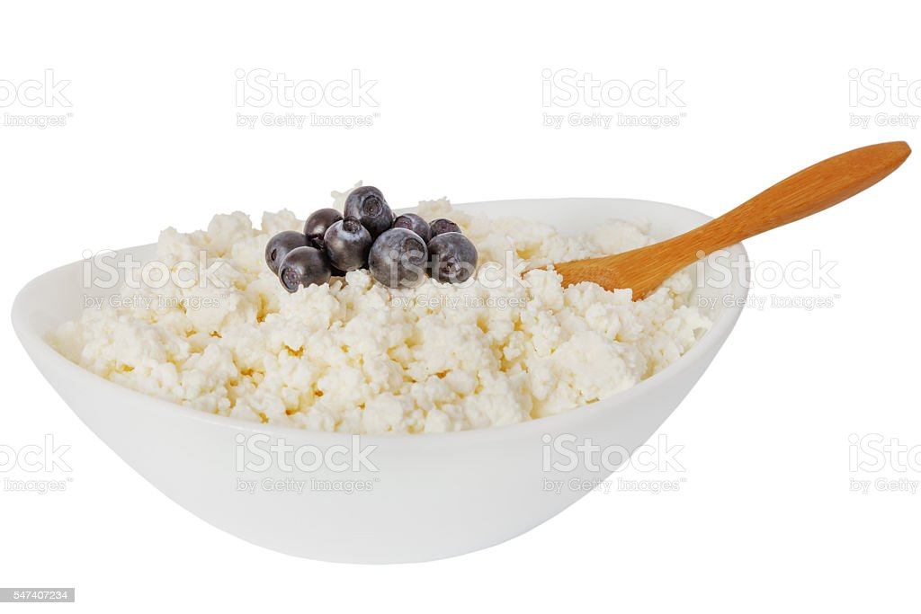 isolated cottage cheese with blueberries and  the wooden spoon stock photo