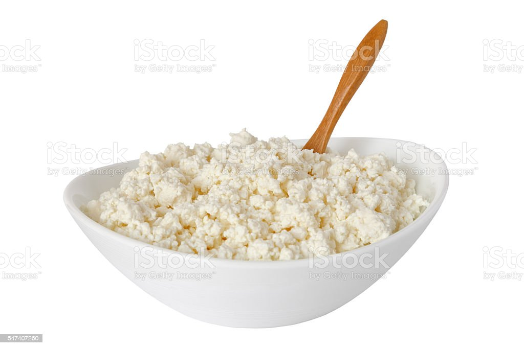 isolated cottage cheese with the wooden spoon in a bowl stock photo