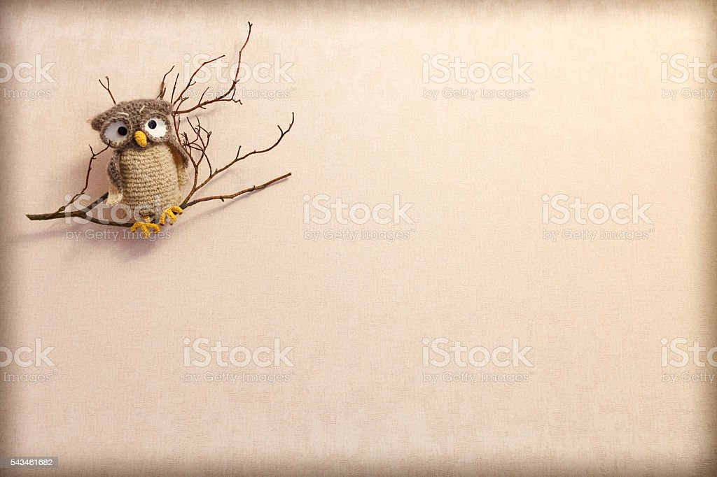 Isolated knitted owl on a branch on a beige background stock photo