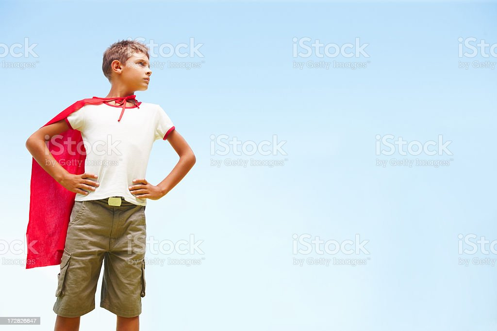 Isolated: Little boy dressed up as a superhero looking away stock photo