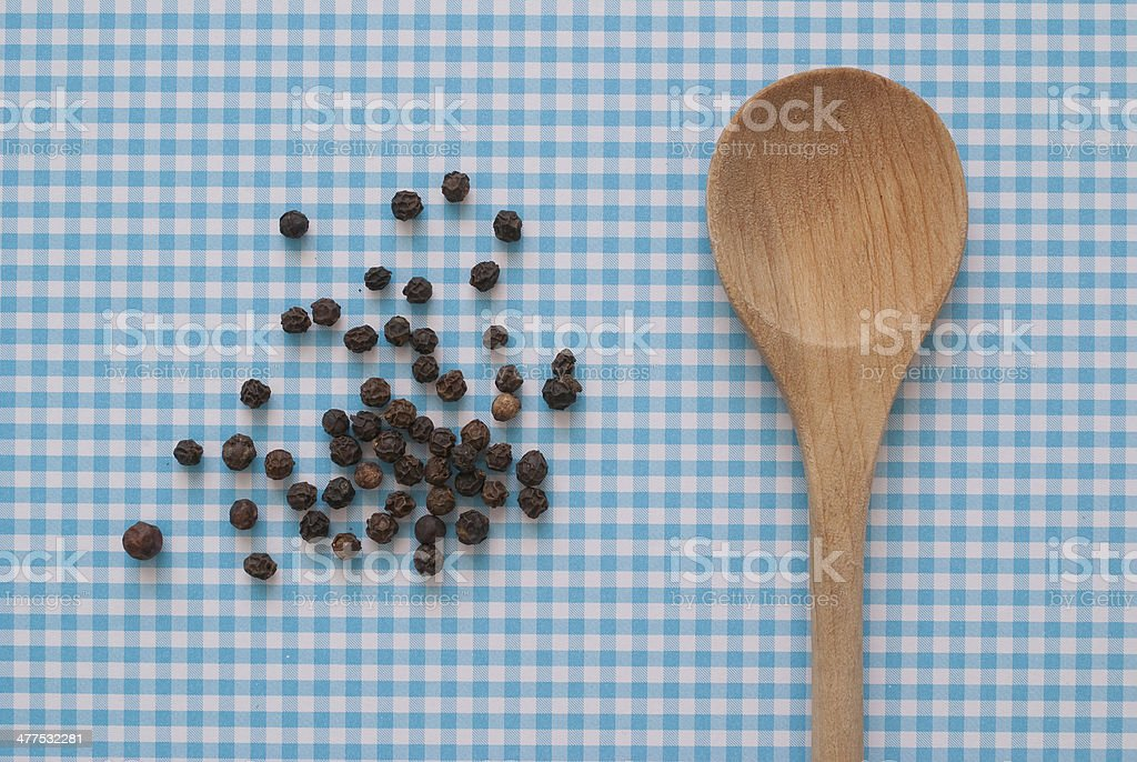 isolated Pepper Corns and wooden spoon on serenity blue background stock photo