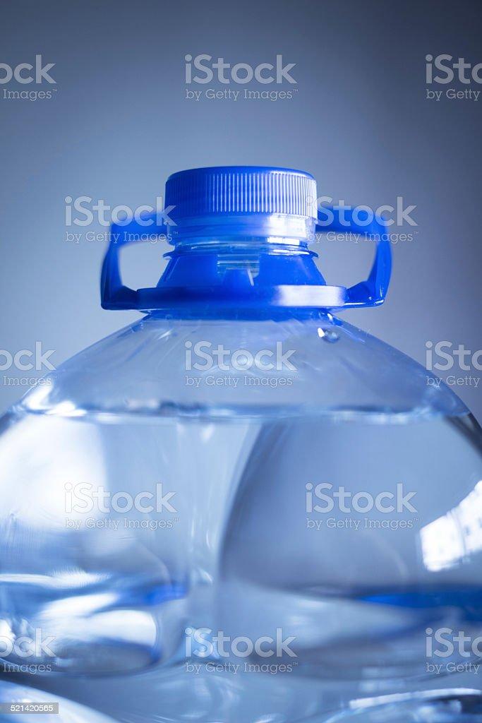 Isolated plastic water bottle plain blue background studio shot close-up stock photo