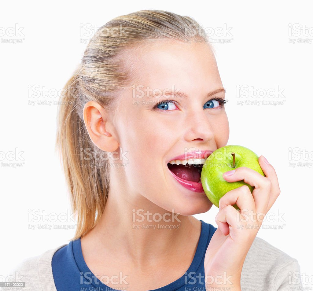 Isolated portrait of young woman eating apple stock photo