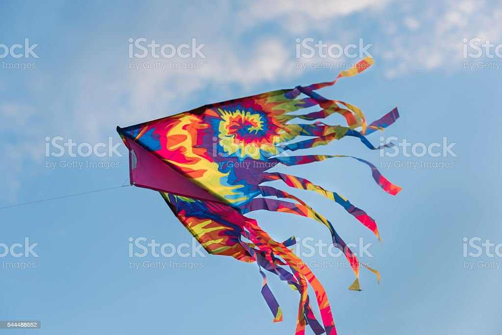 Isolated rainbow kite flying with sky background stock photo