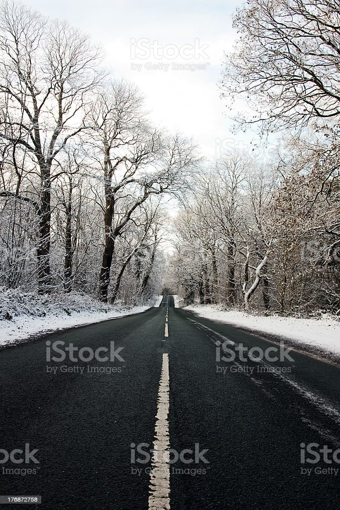 Isolated road through a snow coverd Delamere forest, Cheshire, UK. royalty-free stock photo