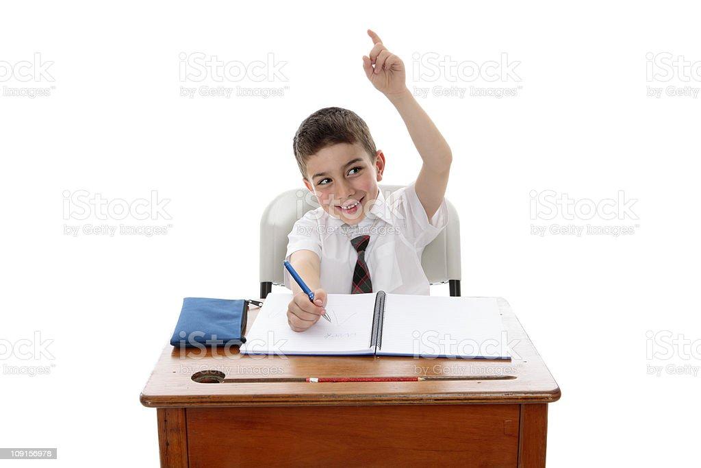 Isolated school boy at desk raising hand royalty-free stock photo