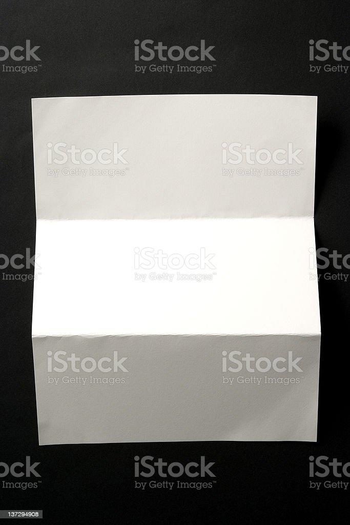 Isolated shot of blank folded paper on black background royalty-free stock photo