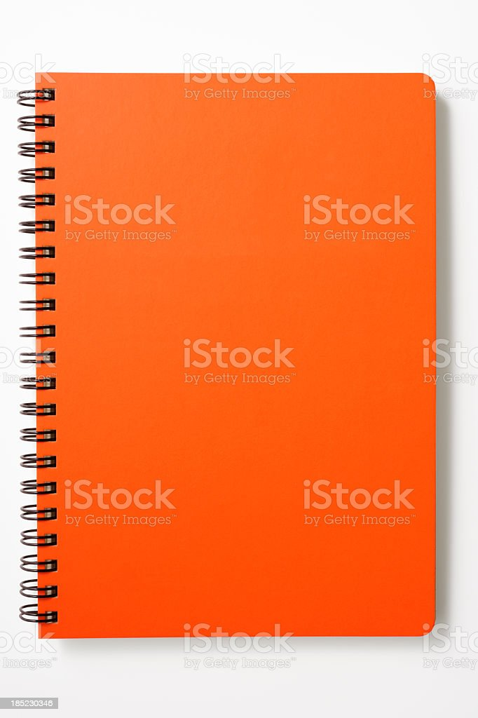 Isolated shot of closed red spiral notebook on white background stock photo