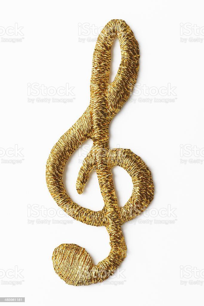 Isolated shot of gold embroidery musical note on white background royalty-free stock photo
